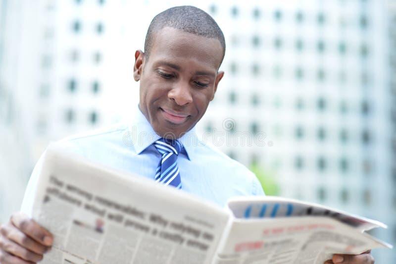 Корпоративные новости чтения человека на outdoors стоковая фотография