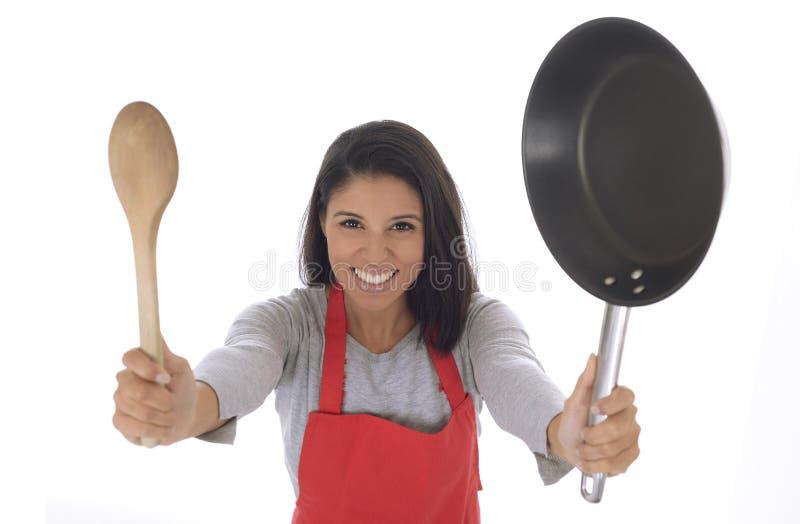Корпоративный портрет молодой привлекательной испанской домашней женщины кашевара в красный представлять рисбермы счастливый и из стоковая фотография rf