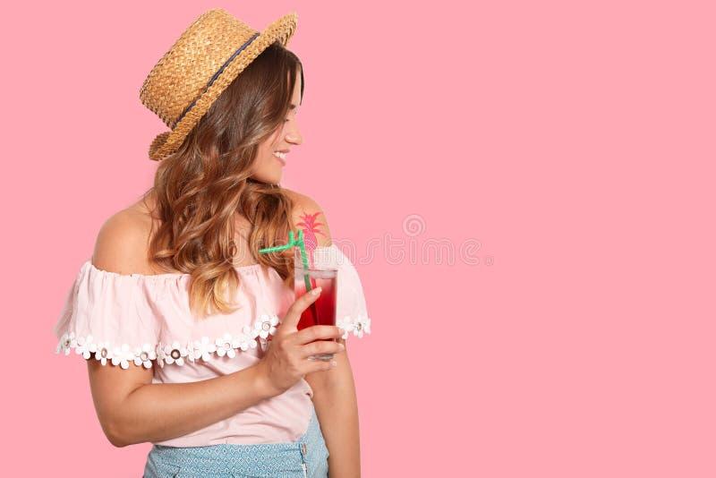 Косая съемка модной женщины в шляпе лета, стильной блузке, наслаждается свежим холодным коктейлем, смотрит прочь, имеет нежное ле стоковые фотографии rf