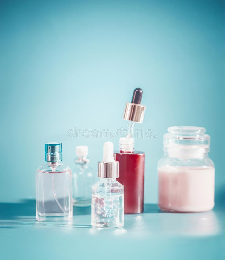 Косметика в контейнерах бутылки Установка заботы кожи с тонером, сутью, сывороткой и сливк на предпосылке сини бирюзы, вид сперед стоковые изображения