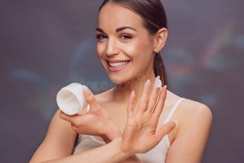 Косметика курорта - молодая женщина играя с сливк для тела, стоковые фото