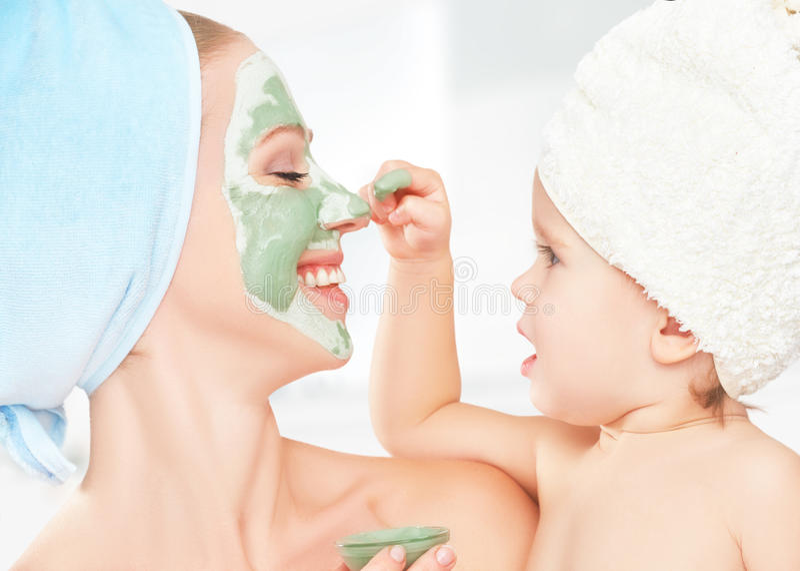 Косметика семьи в ванной комнате ребёнок матери и дочери делает маску для кожи стороны стоковое фото rf