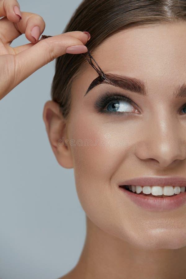Косметики брови Женщина принимая подкраску геля чела от брови стоковая фотография