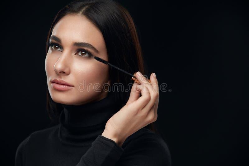 Косметики состава Женщина со стороной красоты прикладывая черную тушь стоковые фотографии rf
