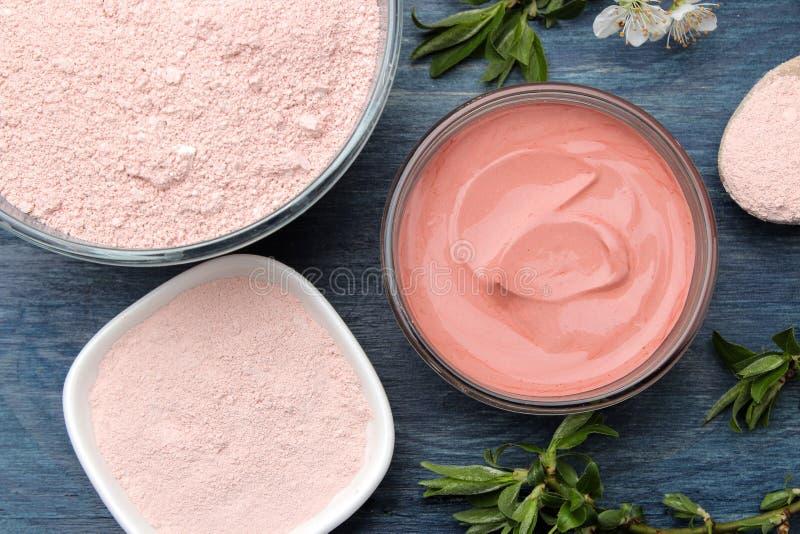Косметическая глина Розовая косметическая глина в разных видах на голубом деревянном столе лицевой щиток гермошлема и тело продук стоковые фото