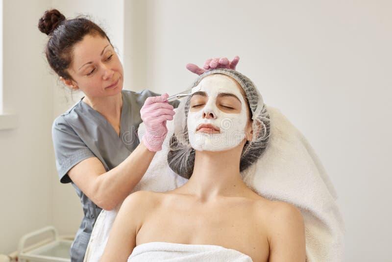 Косметическая процедура спа, концепция skincare Женщина получая лицевую заботу beautician на салоне спа, слезать стороны applays  стоковые фотографии rf