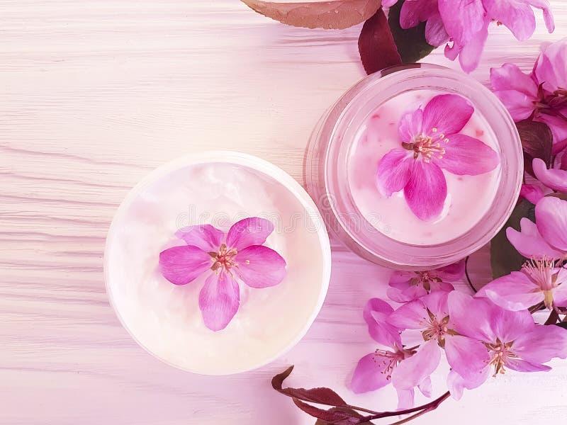 Косметическая сливк, выдержка цветка магнолии на деревянной предпосылке стоковые изображения