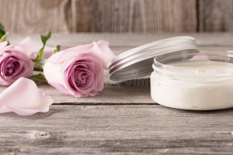 Косметическая сливк с розовыми розами на старом деревянном столе стоковое изображение