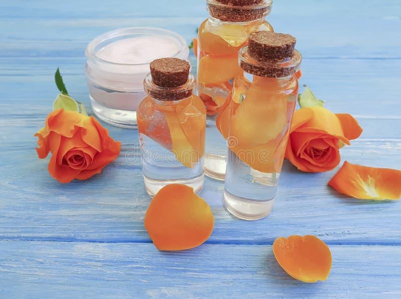 Косметическая сливк, moisturizing выдержка ингредиента, цветок свежести подняла на голубую деревянную предпосылку стоковые изображения