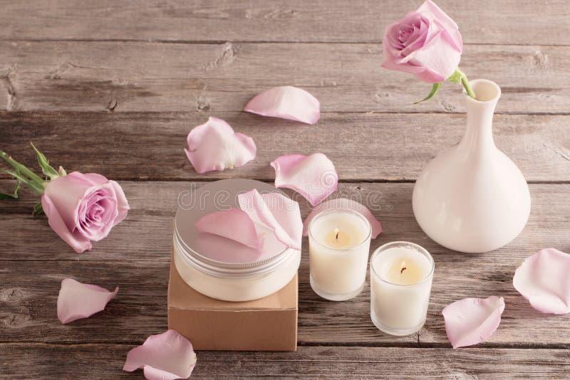 Косметическая сливк с розами и свечой на старом деревянном столе стоковые фото