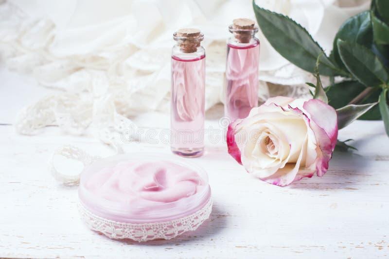 Косметическая сливк с розовыми розами на деревянном столе стоковое фото rf