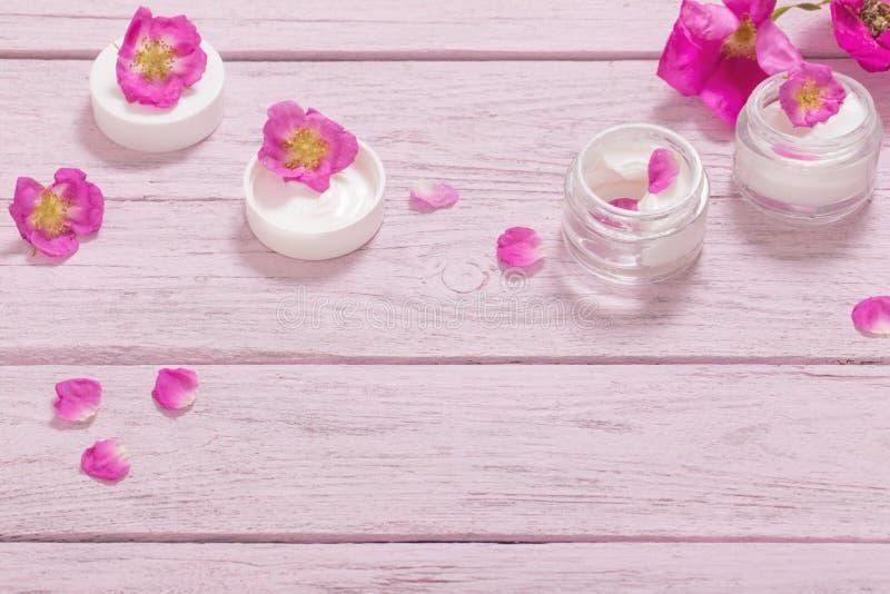 Косметическая сливк с розовыми розами на деревянном столе стоковое изображение rf