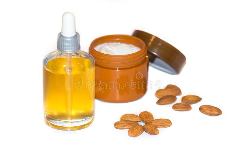 Косметические сливк, миндальное масло и миндалина стороны состава Здоровье для кожи стороны с миндальным маслом, здоровье для вол стоковое фото