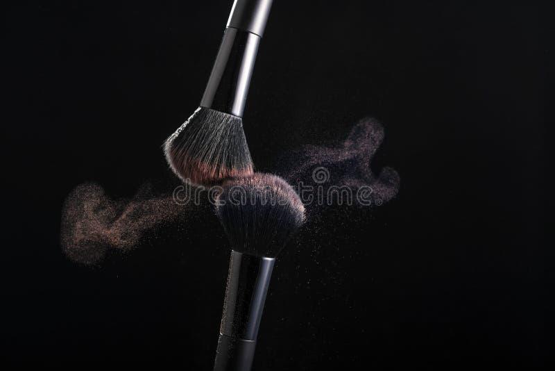 Косметические тени теней другого цвета, разбрасывают от 2 щеток макияжа создавая причудливую картину на черной предпосылке стоковые изображения