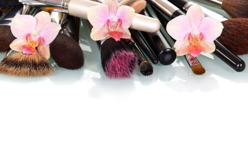 Косметические цветки щетки и орхидеи состава изолированные на белизне стоковая фотография