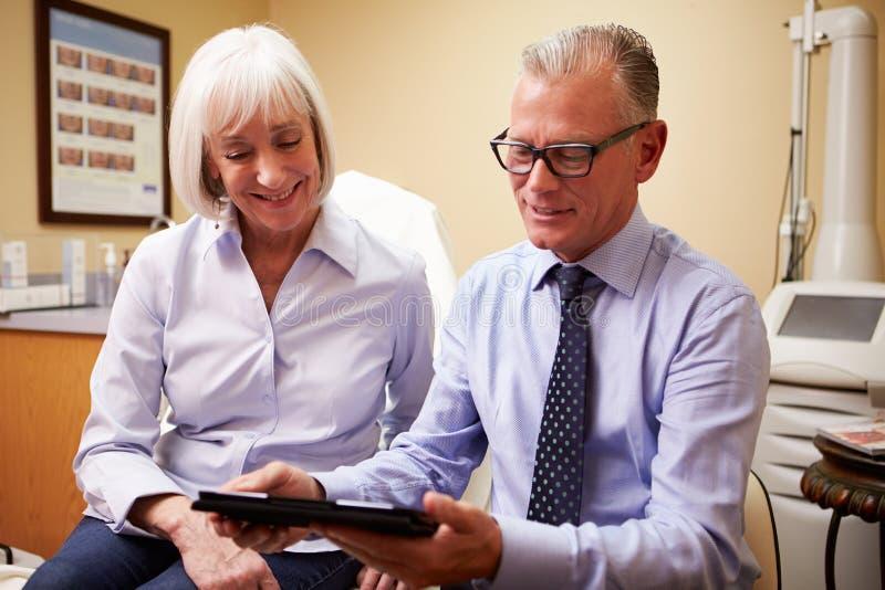 Косметический хирург обсуждая процедуру с клиентом в офисе стоковая фотография rf