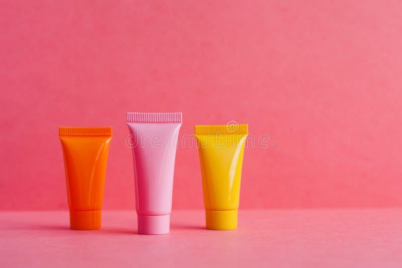 3 3 косметических трубки на розовой предпосылке точки польки Пустые пластмасовые контейнеры, простой шаблон комплексного конструи стоковые фотографии rf