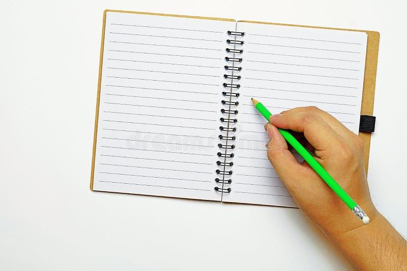 Космос взгляд сверху и экземпляра, рука a держа зеленый карандаш, пробуя написать что-то на книге стоковые фото
