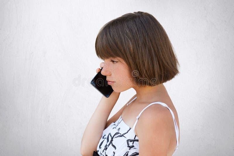 Косой портрет маленькой девочки с качанными волосами, нося белым платьем, говоря над сотовым телефоном с серьезным выражением сти стоковые изображения