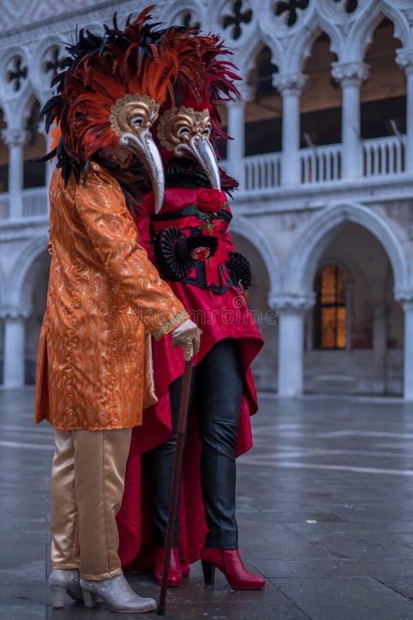 Костюмированные маслениц-ходоки с красным цветом оперились маска стоя в квадрате ` s St Mark во время Венеции Масленицы Carnivale стоковые фотографии rf