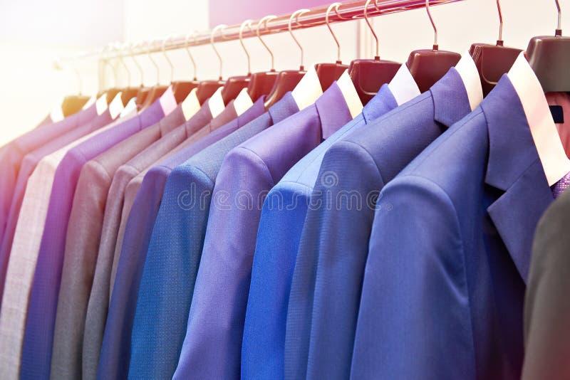Костюмы людей с рубашками в магазине одежды стоковая фотография rf