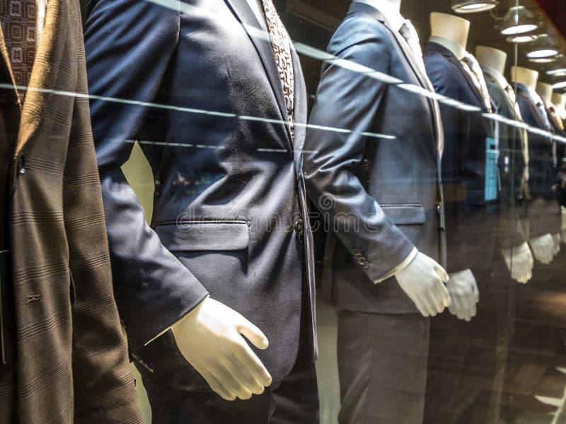 Костюмы людей, с рубашками, связями, брюками и синими пиджаками на дисплее на манекенах перед магазином портноя, на окне стоковое фото