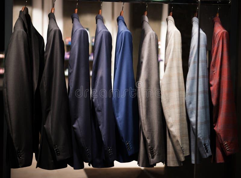 Костюмы людей в магазине моды стоковое изображение rf