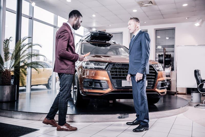 Костюм бизнесмена нося и черные ботинки покупая автомобиль стоковое фото rf