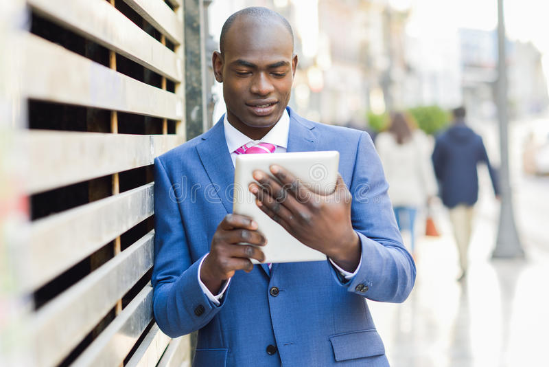 Костюм и связь чернокожего человека нося смотря его планшет стоковое изображение rf