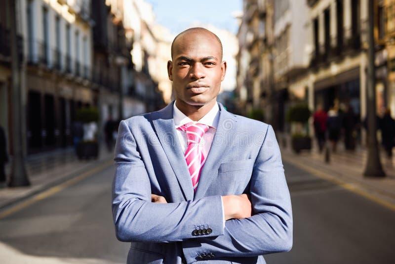 Костюм красивого чернокожего человека нося в городской предпосылке стоковая фотография