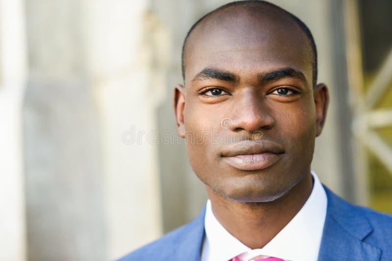 Костюм красивого чернокожего человека нося в городской предпосылке стоковые фото
