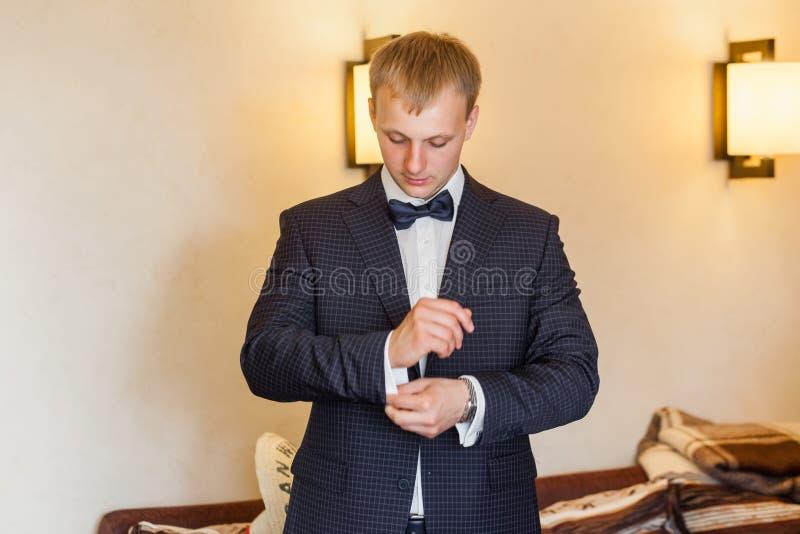 Костюм свадьбы Groom нося и тумаки застегивать стоковая фотография