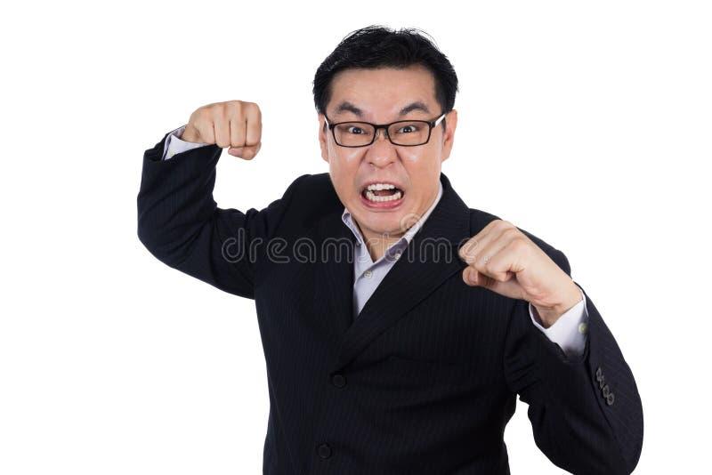 Костюм сердитого азиатского китайского человека нося и держать оба кулак стоковое изображение rf