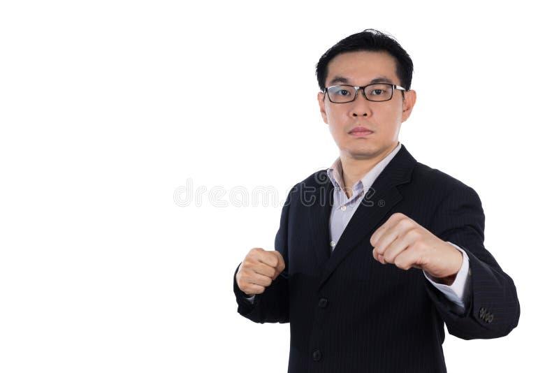 Костюм сердитого азиатского китайского человека нося и держать оба кулак стоковое фото rf