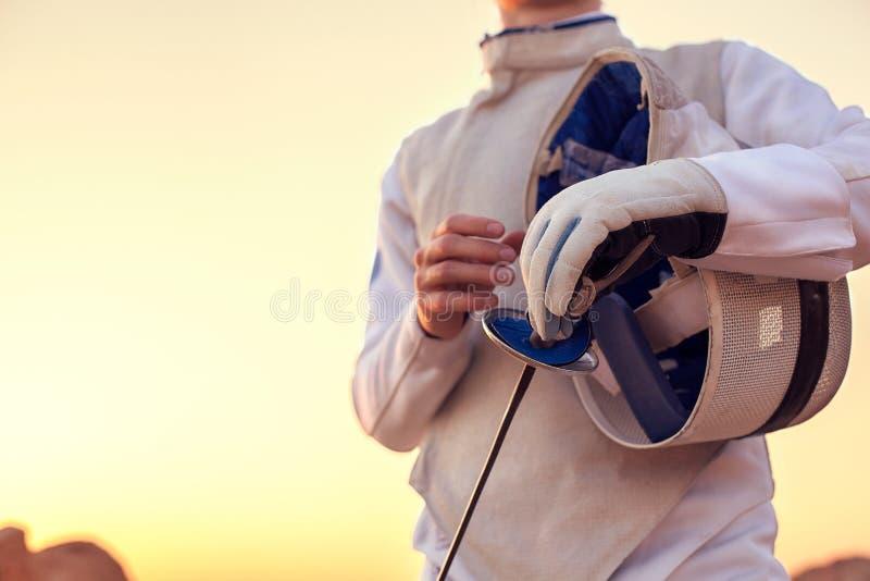Костюм фехтовальщика нося белый ограждая и держать его ограждая маску и шпагу на солнечной предпосылке стоковые фотографии rf