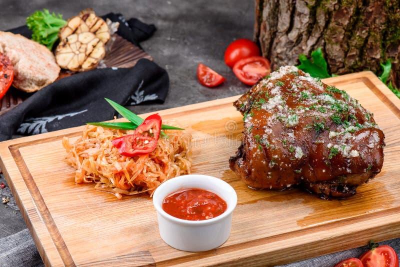 Костяшка свинины на светлой деревянной доске служила с потушенными капустой и соусом барбекю на темной конкретной предпосылке стоковая фотография rf