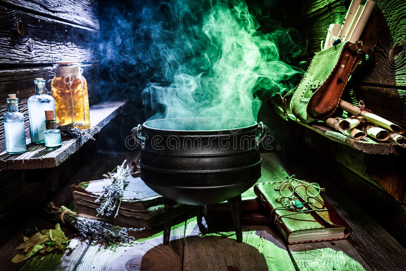 Котел Witcher с голубыми зельями и книгами на хеллоуин стоковые фото