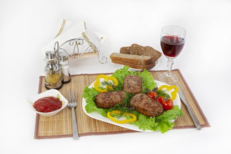 Котлеты с зелеными цветами, томатами и огурцами Служите с черным или белым хлебом и стеклом красного вина стоковые фотографии rf