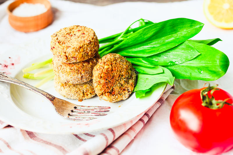 Котлеты чечевицы с паприкой и кашой, зелеными цветами, томатом, vegan стоковое фото