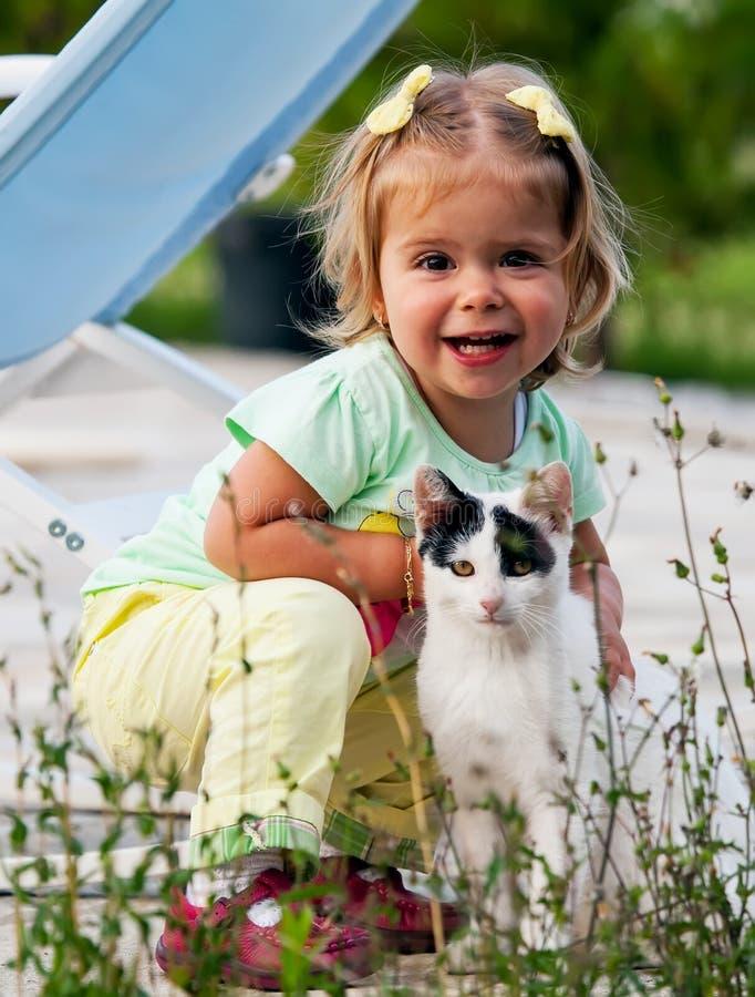 Кот и малая девушка стоковые изображения