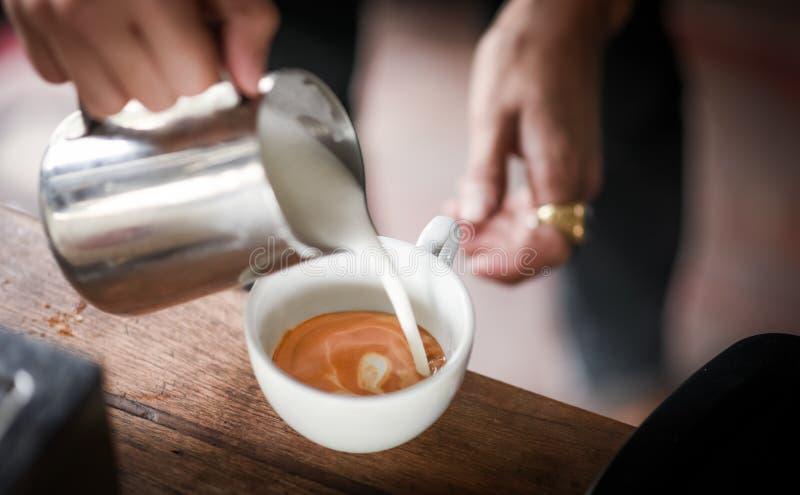 Кофеварка лить молоко для делает искусство latte стоковые фотографии rf
