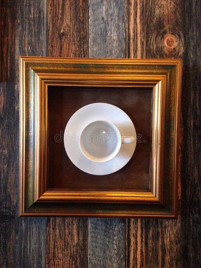 Кофейная чашка в рамке повиснула на стене в демонстрации искусства moder стоковое фото rf