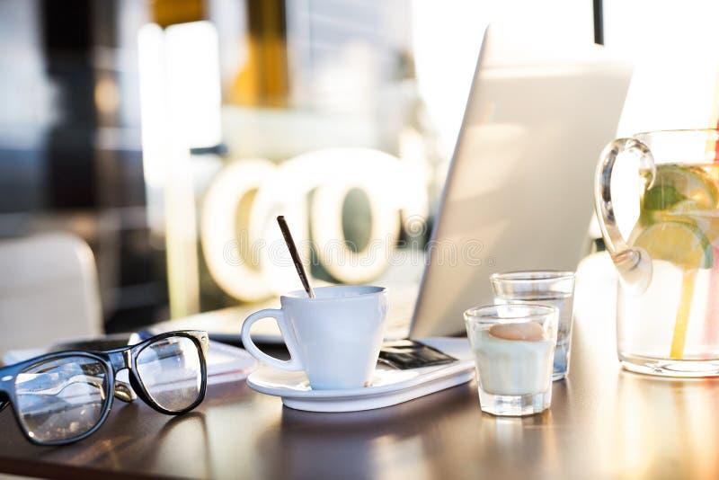 Кофейная чашка, лимонад, eyeglasses и компьтер-книжка клали на таблицу стоковые фото
