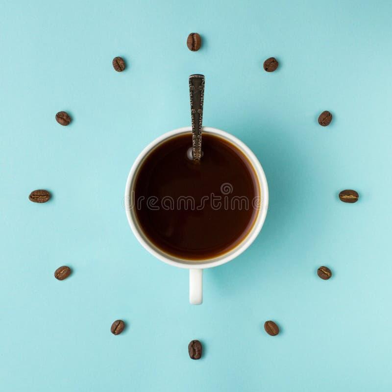 Кофейная чашка и зажаренные в духовке фасоли аранжированные как циферблат на голубой предпосылке, взгляд сверху Символ времени ко стоковые фотографии rf