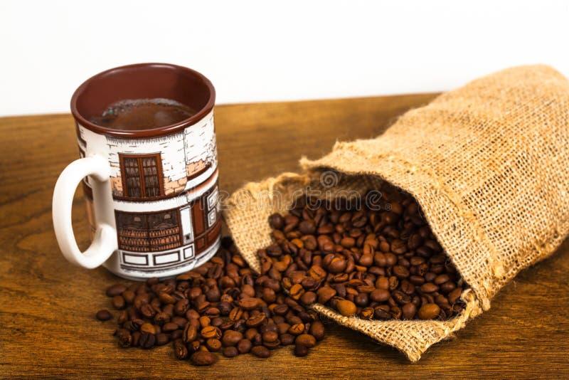 Кофейная чашка и кофейные зерна в мешке кладут в мешки стоковые фото