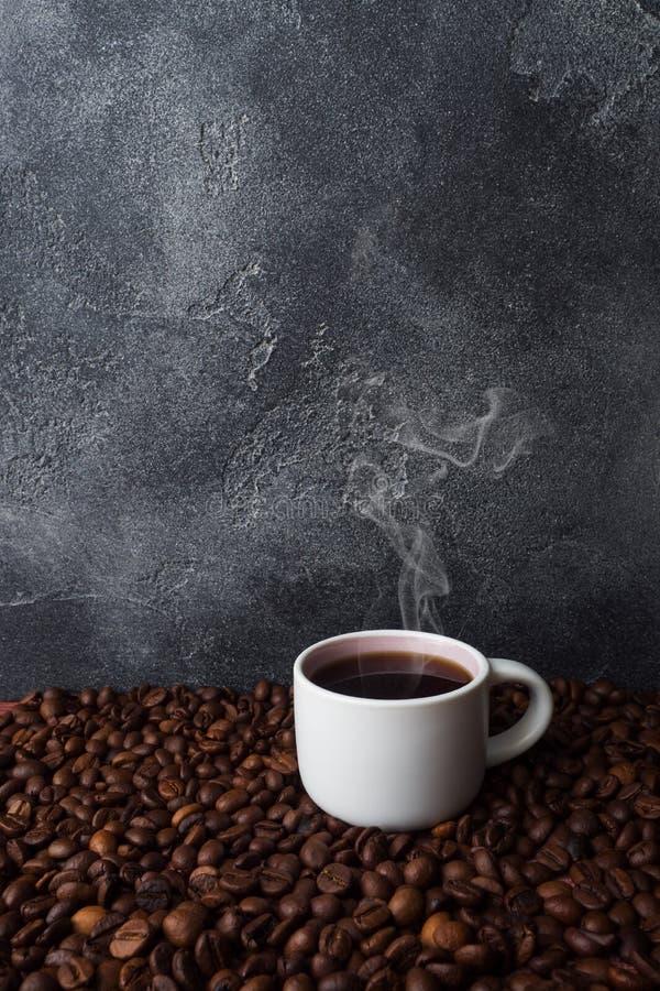 Кофейная чашка и кофейные зерна на темной предпосылке r стоковое изображение rf