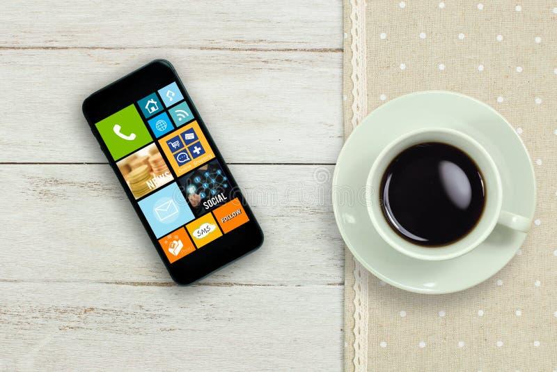 Кофейная чашка и мобильный телефон на деревянной таблице стоковые изображения rf