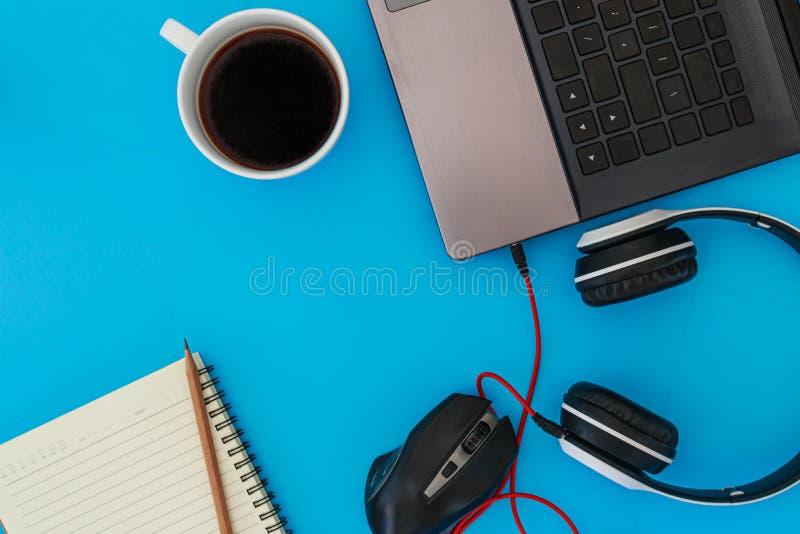 Кофейная чашка и наушники от ноутбука с тетрадью и карандашем стоковое изображение