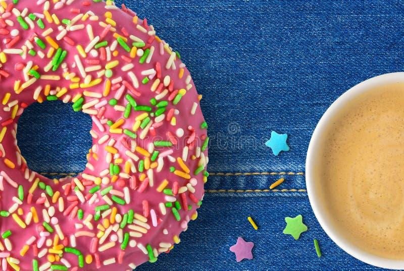 Кофейная чашка и розовый донут стоковые фото