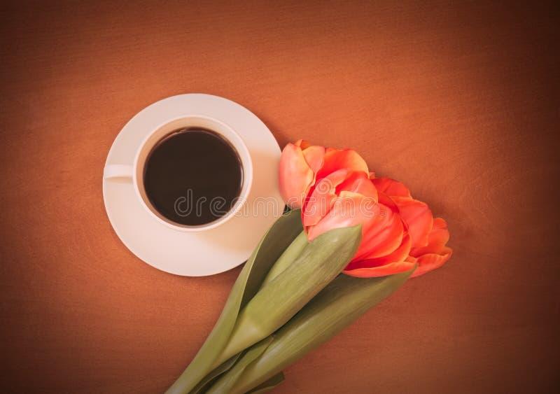 Кофейная чашка и тюльпан апельсина цветут на деревянной предпосылке стоковое изображение